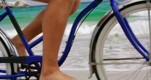 Basse section de l'homme montant une bicyclette sur la plage 4k clips vidéos