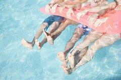 Basse section de quatre amis dans une piscine se tenant sur un radeau gonflable avec des pieds collant hors de l'eau Photographie stock libre de droits