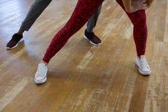 Basse section des amis préparant la danse sur le plancher en bois Photographie stock