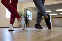 Basse section des amis pratiquant la danse sur le plancher Photographie stock