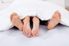 Basse section des couples intimes sous la couverture Photo libre de droits
