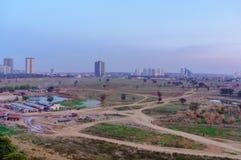 Bassifondi, campi vuoti dell'azienda agricola con i grattacieli nei precedenti nell'ncr di Delhi del gurgaon immagine stock