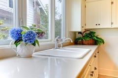 Bassin de cuisine avec les modules et les fleurs blancs. Images stock