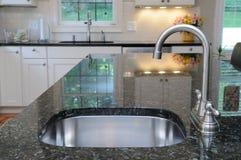 Bassin de cuisine sur le compteur de granit Photos stock