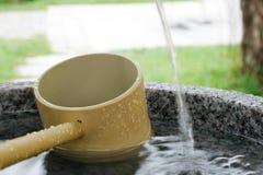 Bassin en pierre japonais de l'eau avec la poche en bambou Photographie stock libre de droits