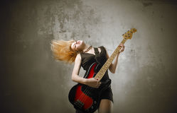 Bassist. Portrait of a woman playing the bass guitar while moving her hair Royalty Free Stock Images