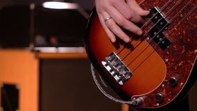 Bassist. Close-up on a male hand playing bass. Blurry amplifier & speaker box in background stock video