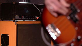 Bassist. Close-up on a male hand playing bass. Bassist. Defocus from amplifier & speaker box in background to close-up on a male hand playing bass stock footage
