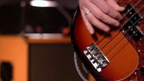 Bassist. Defocus on a male hand playing bass. Close-Up. Amplifier & speaker box in background stock video footage