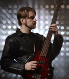 Bassist playing a custom made bass guitar. Studio stock image