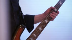 Bassist plays bass guitar. The camera moves along the neck of the guitar stock footage