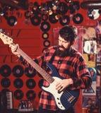 Bassistkonzept Mann s hält Bass-Gitarre, Spielmusik im Vereinatmosphärenhintergrund Musiker, Künstlerspiel elektrisch stockbilder