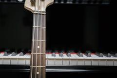 Basso elettrico contro le chiavi del pianoforte a coda Fotografia Stock