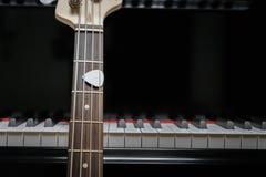 Basso elettrico contro le chiavi del pianoforte a coda Fotografia Stock Libera da Diritti