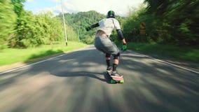 Basso molto veloce del pattino di longboard di guida del giovane la strada principale, attività estrema del pattino di sport di e stock footage
