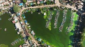 Basso superiore aereo del villaggio dei pescatori al fiume inquinante con le alghe verdi archivi video