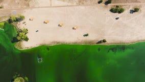 Basso superiore aereo della spiaggia sabbiosa vuota da acqua inquinante molto con le alghe verdi archivi video