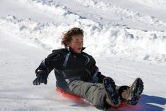 Basso veloce di Sledding del ragazzo la collina su una slitta rossa fotografia stock
