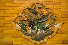 Bassorilievo cinese antico sul muro di mattoni arancio Immagini Stock Libere da Diritti