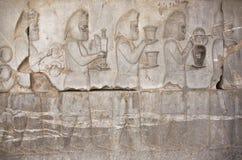 Bassorilievo di pietra con la gente antica che tiene alimento e le armi orlate in Persepolis, Iran Fotografie Stock Libere da Diritti