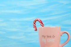 Bastão cor-de-rosa do pirulito do copo C no fundo azul com texto meu chá e meu café Vista horizontal, espaço da cópia, cores past imagens de stock