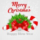 Bastão de doces do Natal com azevinho e curva vermelha Fotos de Stock Royalty Free