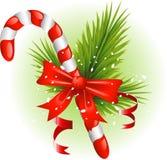 Bastão de doces do Natal decorado com filiais do pinho Fotografia de Stock