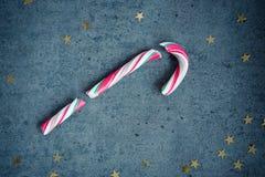 Bastão de doces no fundo concreto cinzento com estrelas douradas Fundo do Natal Fotografia de Stock