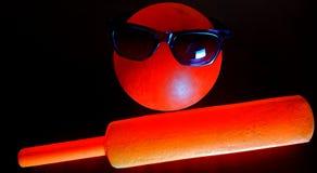Bast?o de grilo com futebol na imagem conservada em estoque da cor vermelha foto de stock royalty free