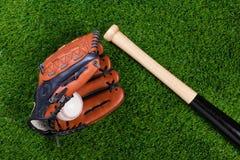 Bastão e esfera da luva de basebol na grama Fotografia de Stock Royalty Free