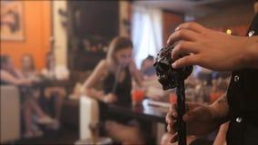 Bastão preto sob a forma do crânio nas mãos dos homens O fundo não é no foco o interior do restaurante com video estoque