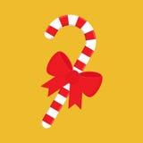 Bastón de caramelo de la Navidad con el arco rojo Imagenes de archivo