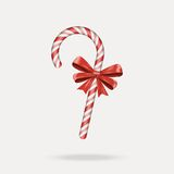 Bastón de caramelo de la Navidad con el arco rojo aislado en el fondo blanco Imágenes de archivo libres de regalías