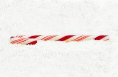 Bastón de caramelo de la Navidad en una nieve Foto de archivo libre de regalías