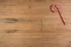 Bastón de caramelo en tabla de cortar gastada Fotos de archivo libres de regalías