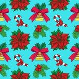 Bastón de caramelo de la Navidad, acebo y poinsetia, campana con la cinta en fondo azul Fotos de archivo libres de regalías