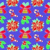 Bastón de caramelo de la Navidad, acebo y poinsetia, campana con la cinta en fondo azul con el esquema blanco Imagen de archivo