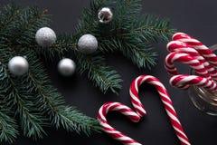 Bastón de caramelo de la Navidad con las bolas de plata de la tarde y árbol de abeto verde en fondo negro Fotos de archivo libres de regalías