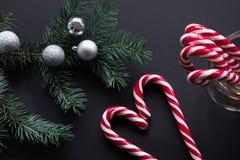 Bastón de caramelo de la Navidad con las bolas de plata de la tarde y árbol de abeto verde en fondo negro Concepto de la Navidad  Imágenes de archivo libres de regalías