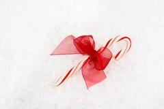 Bastón de caramelo rojo y blanco con el arqueamiento rojo Fotos de archivo