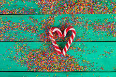 Bastón de la Navidad en una forma y un color del corazón que asperjan en fondo de madera de la turquesa Fotografía de archivo