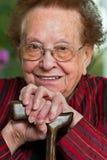 Bastón mayor lisiado con una sonrisa Foto de archivo