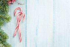 Bastón y árbol de navidad de caramelo en la tabla de madera Fotos de archivo
