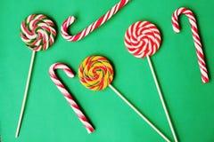 Bastões de doces coloridos do Natal no fundo verde Imagem de Stock Royalty Free