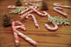 Bastões de doces dispersados na tabela de madeira com cones e flocos de neve do pinho Imagem de Stock Royalty Free