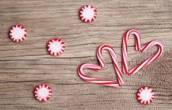Bastões de doces do Natal na forma do coração e nos doces de pastilha de hortelã Fotos de Stock