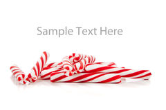 Bastões de doces vermelhos e brancos no branco com espaço da cópia Imagens de Stock