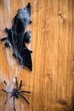 Bastões dos símbolos de Dia das Bruxas, Web e aranhas pretas em Backgrou de madeira Fotografia de Stock Royalty Free