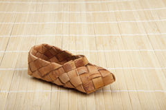 Bast shoes. Bast, ancient russian shoes on wooden floor Royalty Free Stock Photos