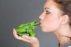 Bastante adolescente besando una rana Foto de archivo libre de regalías